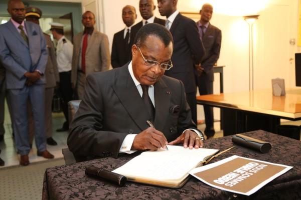 Denis Sassou N'Guesso signant le livre de condoléances à l'ambassade de France à Brazzaville