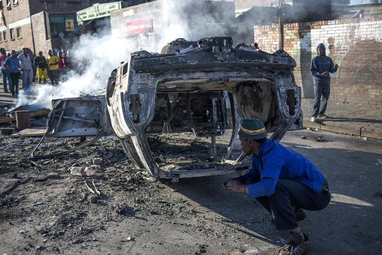 Une voiture brûlée après des violences xénophobes dans le quartier de Jeppestown, à Johannesburg, le 17 avril 2015
