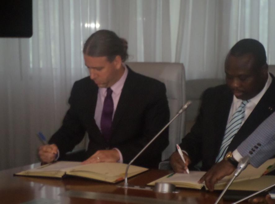 Matthew Steil et Jean Jacques Bouya signant le document
