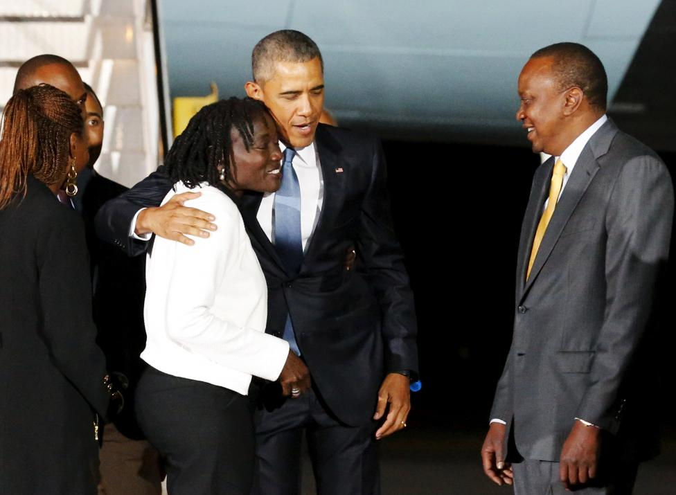 U.S. President Barack Obama (2nd L) embraces his half-sister Auma Obama (L) and is greeted by Kenya's President Uhuru Kenyatta (R) as he arrives aboard Air Force One at Jomo Kenyatta International Airport in Nairobi July 24, 2015. REUTERS/Jonathan Ernst