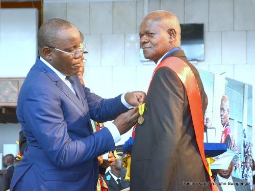 De gauche à droite, le président de l'Assemblée nationale congolaise, Aubin Minaku décore l'artiste photographe congolais, Etienne Kokolo à Kinshasa, le 29/12/2015 lors de la remise des médailles de mérite des arts, science et lettres.