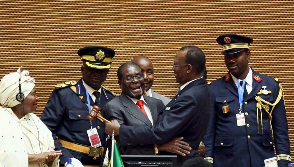 Le président du Zimbawe Robert Mugabe (au centre) dans les bras de son homologue tchadien Idriss Déby lors du passage de témoin à la tête de l'Union africaine, le 30 janvier 2016 à Addis-Abeba. |© REUTERS/Tiksa Negeri