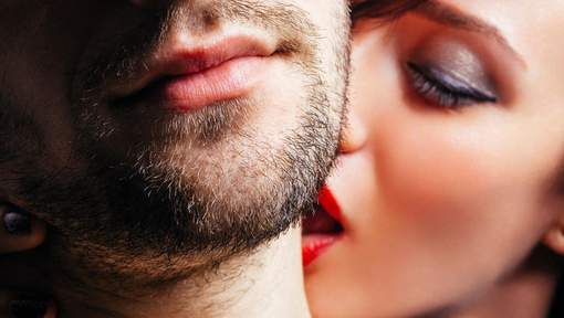 Close up of a women passionately kissing a man on the neck.